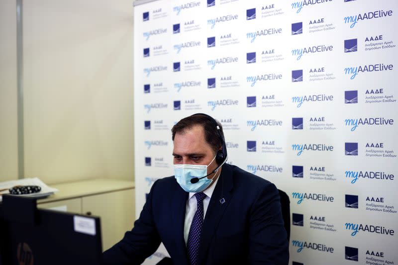 Head of the State Independent Authority of Public Revenue George Pitsilis speaks to a citizen via teleconference in Athens