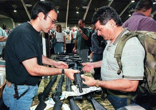 File photo shows a US gun salesman demonstrating a semi-automatic weapon to a potential customer in California. Experts say that in the regions of US states that run along the Mexican border there are some 9,000 gun stores