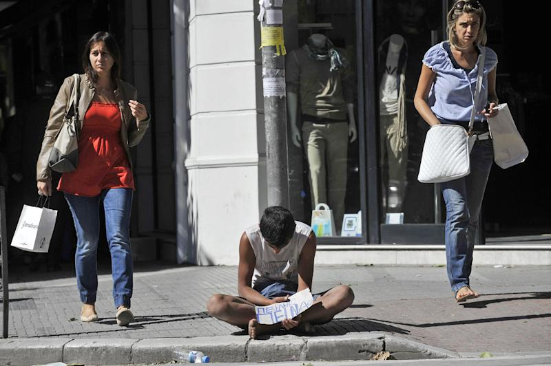 "A man holds a peice of paper which reads in Greek ""I am hungry"" as women walk by in the northern port city of Thessaloniki, Greece, on Friday, Sept. 21, 2012. The leaders of Italy and Greece are insisting on the ""absolute need"" to preserve the eurozone, as Greek politicians struggle to put together an austerity package critical to the country's financial survival.(AP Photo/Nikolas Giakoumidis)"