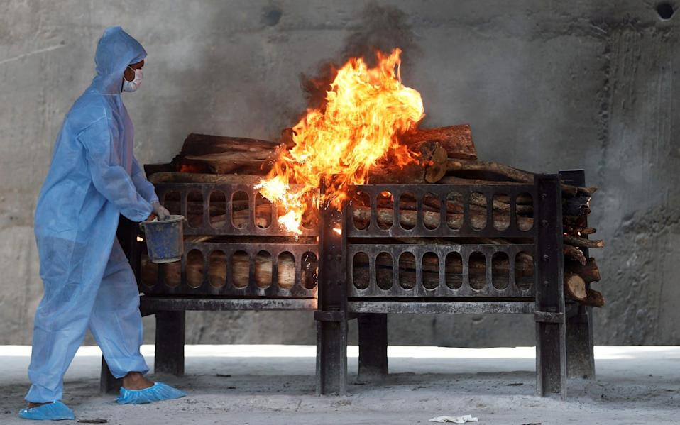 A frontline worker in PPE sprays a flammable liquid on a burning funeral pyre for a coronavirus victim - Reuters