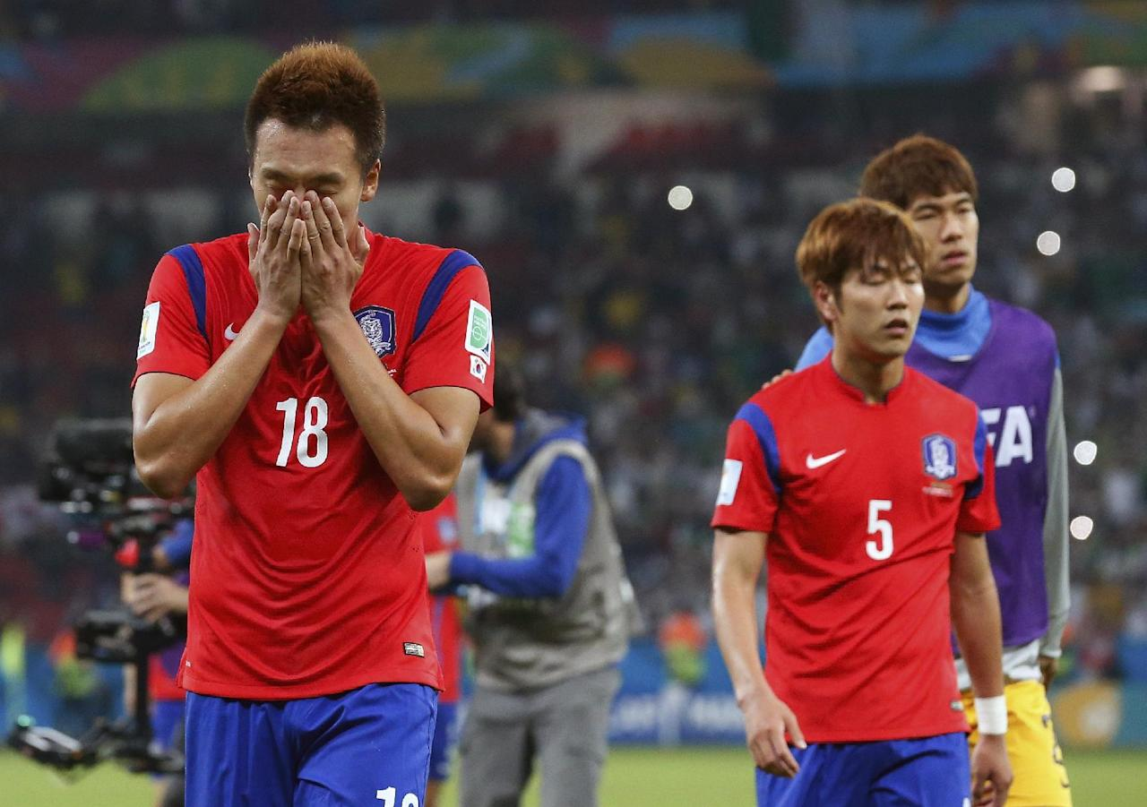 South Korea's Kim Shin-wook (18) walks off the pitch with his teammates after Algeria's 4-2 victory over South Korea during the group H World Cup soccer match between South Korea and Algeria at the Estadio Beira-Rio in Porto Alegre, Brazil, Sunday, June 22, 2014. (AP Photo/Jon Super)
