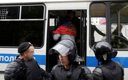 FILE PHOTO: Riot police detain a man covered with Russian national flag during an anti-corruption protest organised by opposition leader Alexei Navalny, on Tverskaya Street in central Moscow, Russia, June 12, 2017. REUTERS/Tatyana Makeyeva/File Photo