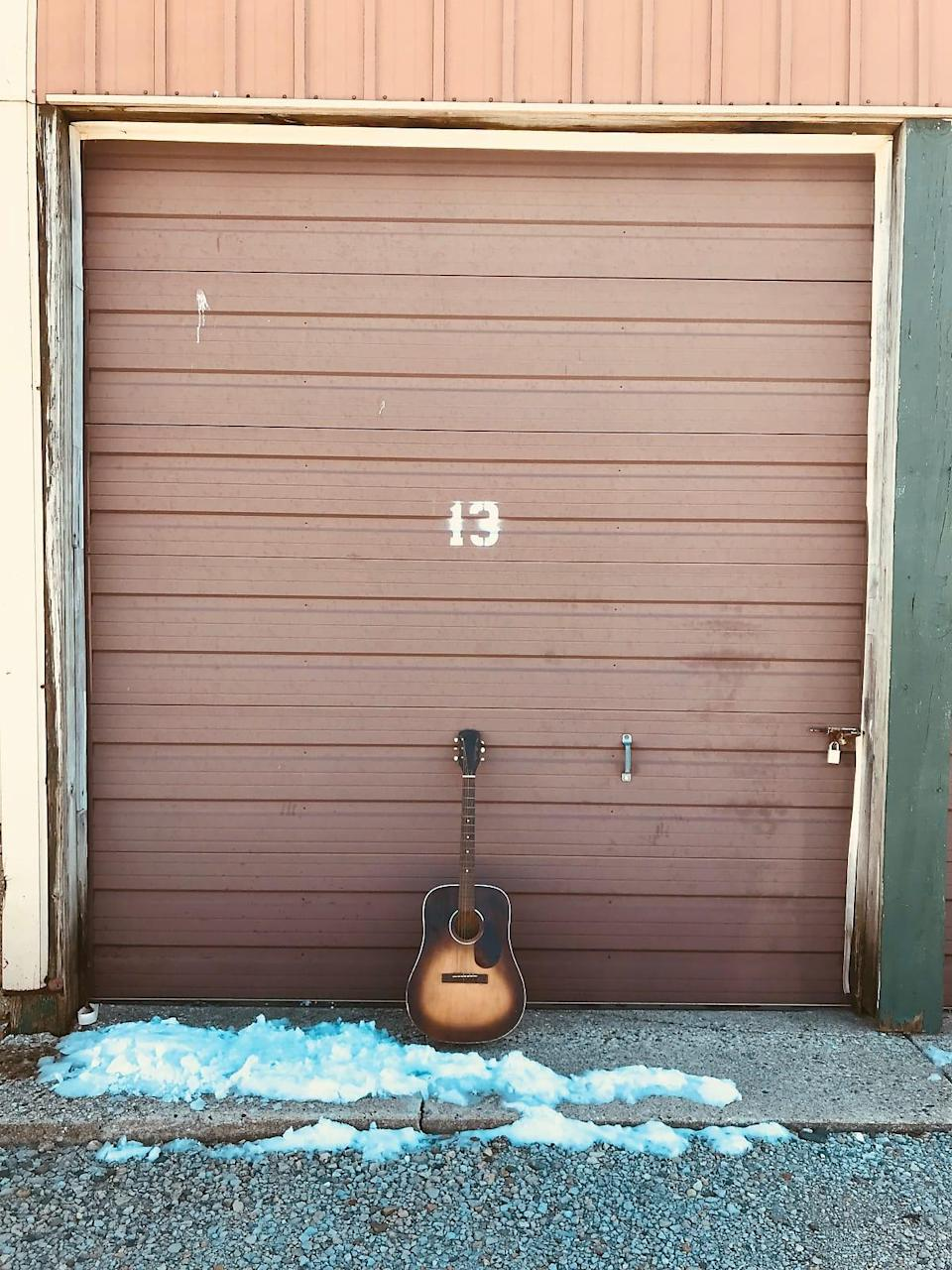 An acoustic guitar sits against a storage door with the number 13 on it
