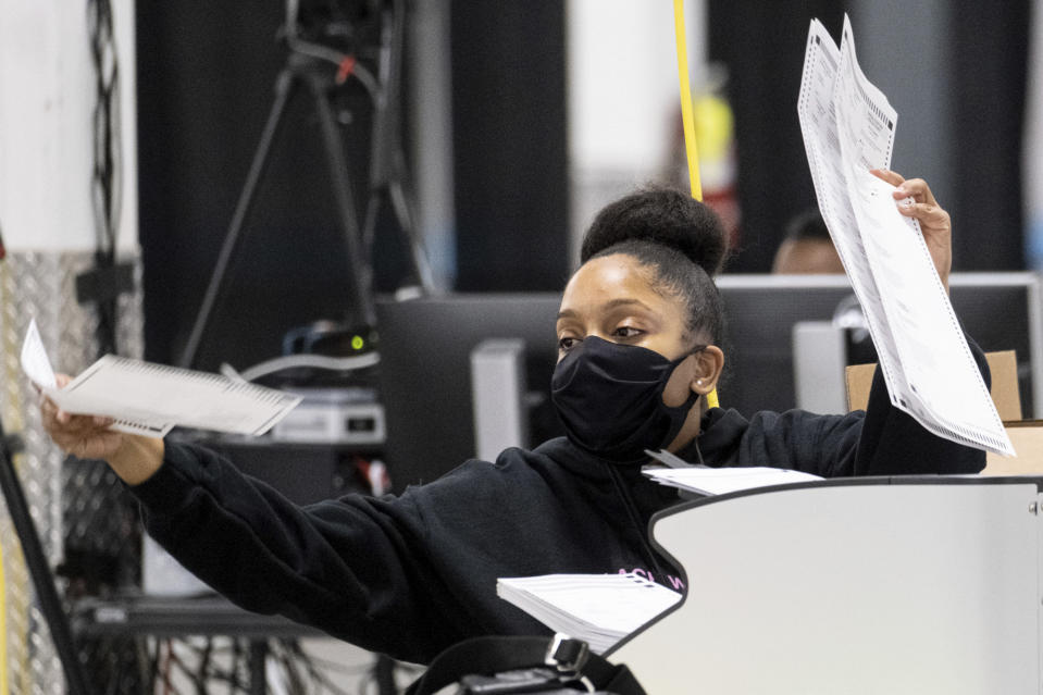 A worker scans ballots as the presidential recount process gets under way Tuesday afternoon, Nov. 24, 2020 in the DeKalb County, Ga. (AP Photo/Ben Gray)