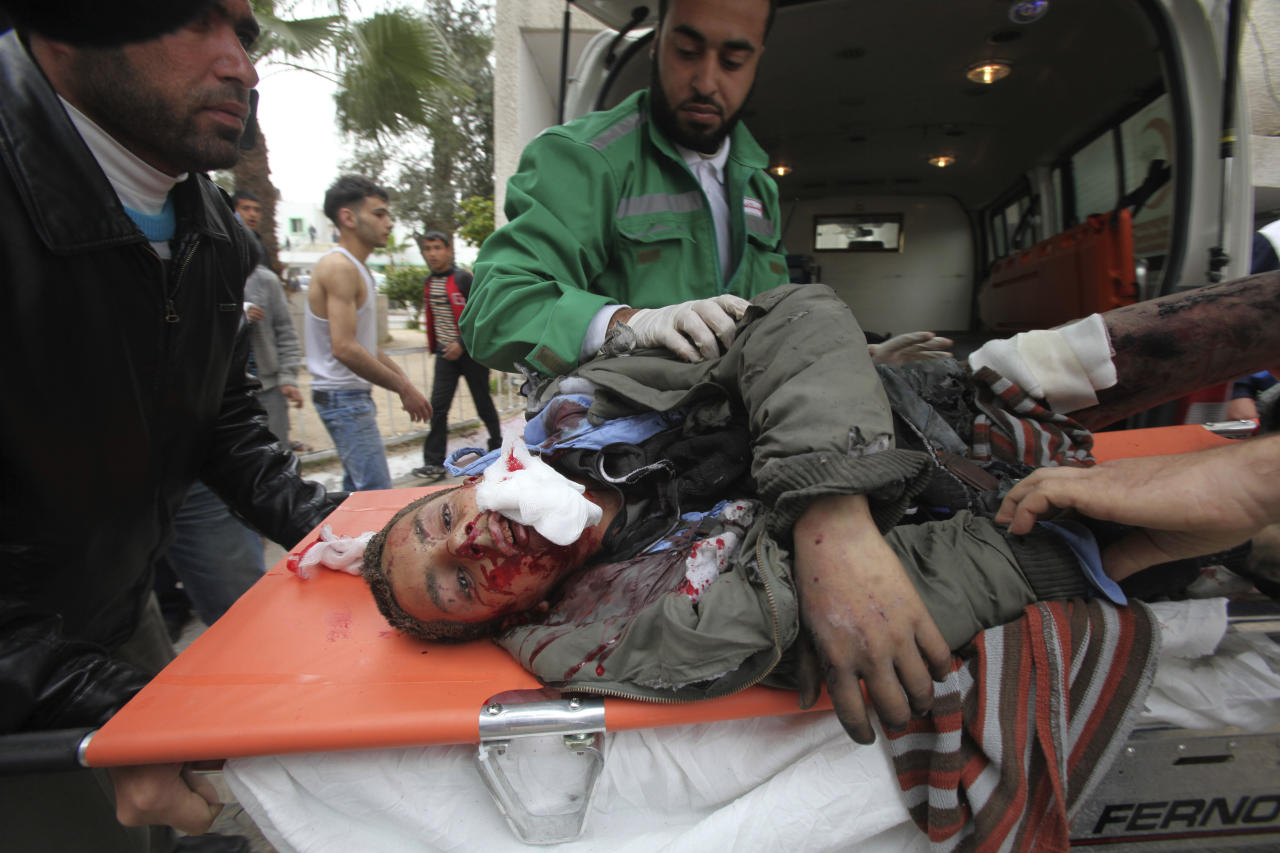 Palestinian medics wheel a wounded man to the treatment room of Shifa hospital following an Israeli air strike in Gaza City, Monday, March 12, 2012. Israeli airstrikes killed two Palestinian militants and a schoolboy in the Gaza Strip on Monday and Palestinian rocket squads barraged southern Israel, in escalating fighting that has defied international truce efforts. (AP Photo/Yasser Qudih)