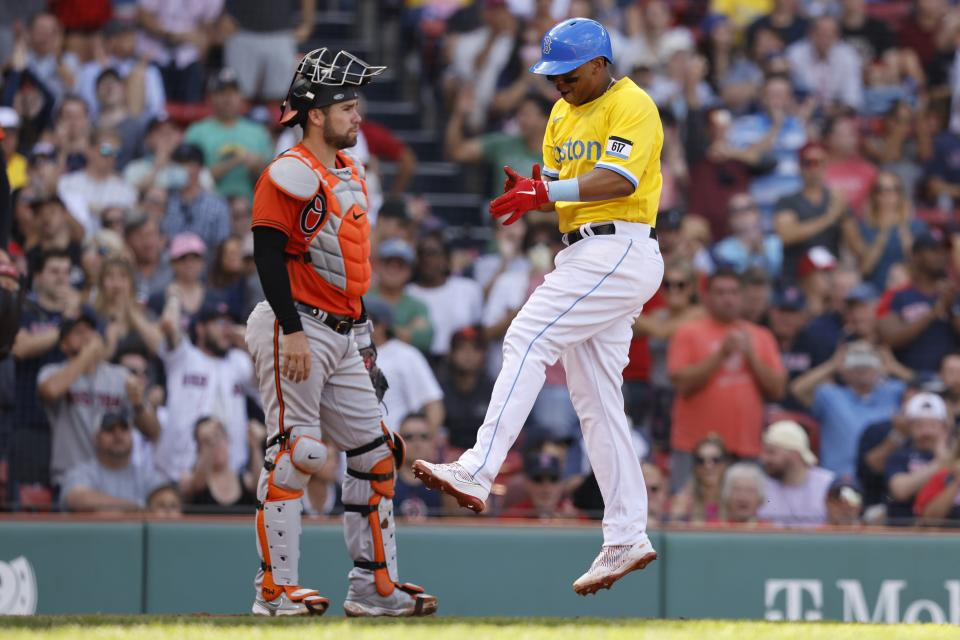 Boston Red Sox's Rafael Devers, right, celebrates in front of Baltimore Orioles' Austin Wynns after scoring on a single by Xander Bogaerts during the fifth inning of a baseball game, Saturday, Sept. 18, 2021, in Boston. (AP Photo/Michael Dwyer)