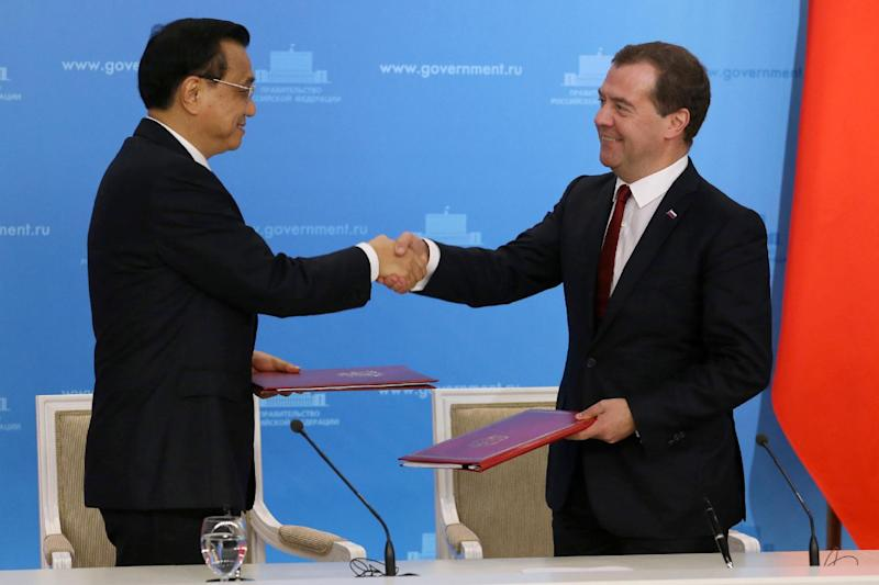 Russia's Prime Minister Dmitry Medvedev (R) and China's Prime Minister Li Keqiang shakes hands during a signing ceremony in Moscow on October 13, 2014 (AFP Photo/Ekaterina Shtukina)