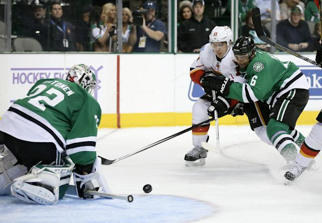 Dallas Stars goalie Kari Lehtonen (32), of Finland, reaches down to block a shot by Calgary Flames' Mikael Backlund (11), of Sweden, as Stars' Trevor Daley (6) assists with the pressure in the second period of an NHL hockey game on Thursday, Oct. 24, 2013, in Dallas. (AP Photo/Tony Gutierrez)