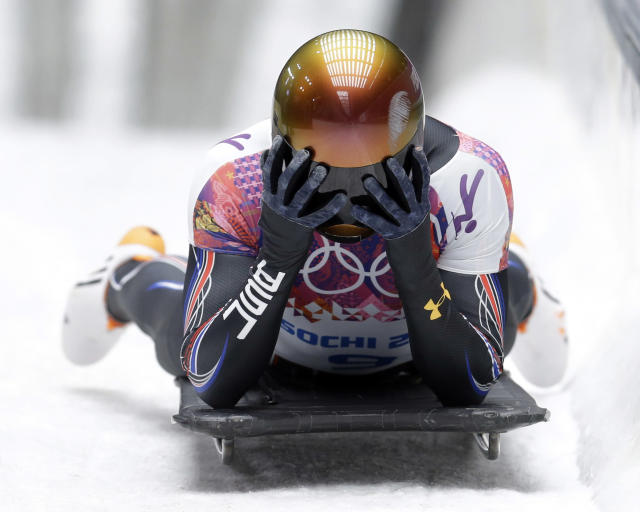 John Daly of the United States puts his head in his hands after a bad final run that dropped him out of medal contention during the men's skeleton competition at the 2014 Winter Olympics, Saturday, Feb. 15, 2014, in Krasnaya Polyana, Russia. (AP Photo/Natacha Pisarenko)