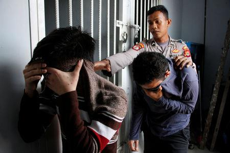 Two Indonesian men, who were later sentenced to 85 lashes of the cane for having sex together, are escorted by police into an Islamic court in Banda Aceh, Aceh province