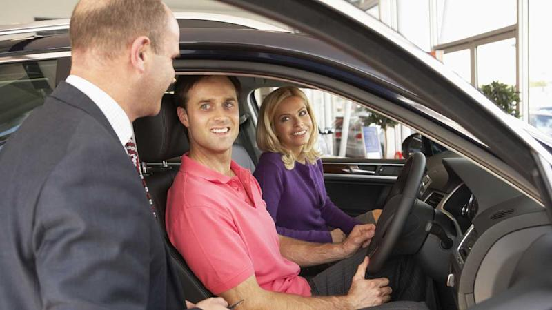 Couple with salesman buying new car at dealership