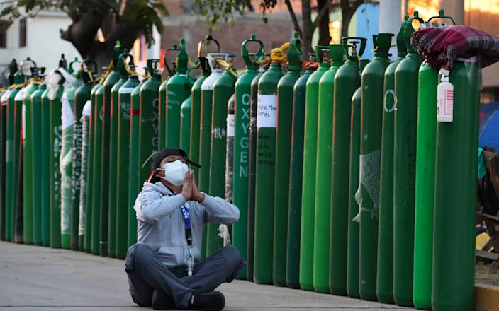 A man prays after waiting three days next to an empty oxygen tank for his uncle who has Covid-19 outside a refill shop in Callao, Peru - AP