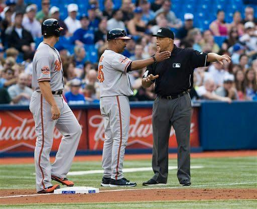 Baltimore Orioles coach DeMarlo Hale, center, argues with umpire Kerwin Danley after Chris Davis, left, was called out while stealing third against the Toronto Blue Jays during third inning of a baseball game in Toronto Monday May 28, 2012. (AP Photo/The Canadian Press, Aaron Vincent Elkaim)