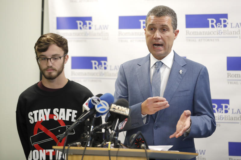 Attorney Antonio Romanucci, right, announces the filing of a civil lawsuit against e-cigarette maker Juul on behalf of his client Adam Hergenreder, left, during a news conference Friday, Sept. 13, 2019, in Chicago. The lawsuit filed Friday in Lake County, Illinois, Circuit Court alleges Juul Labs, Inc., deliberately targeted young people through Instagram and other sites to suggest vaping can boost their social status. It also says Juul doesn't fully disclose their products contain dangerous chemicals. (AP Photo/Charles Rex Arbogast)