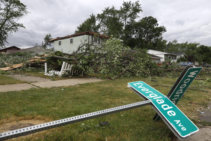 A fallen street sign lays on the ground near a damaged home after a tornado passed through the area on Monday, June 21, 2021, in Woodridge, Ill. (AP Photo/Shafkat Anowar)