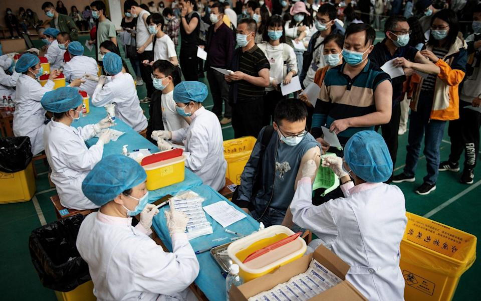 University students in Wuhan queue to receive the China National Biotec Group (CNBG) vaccine - AFP