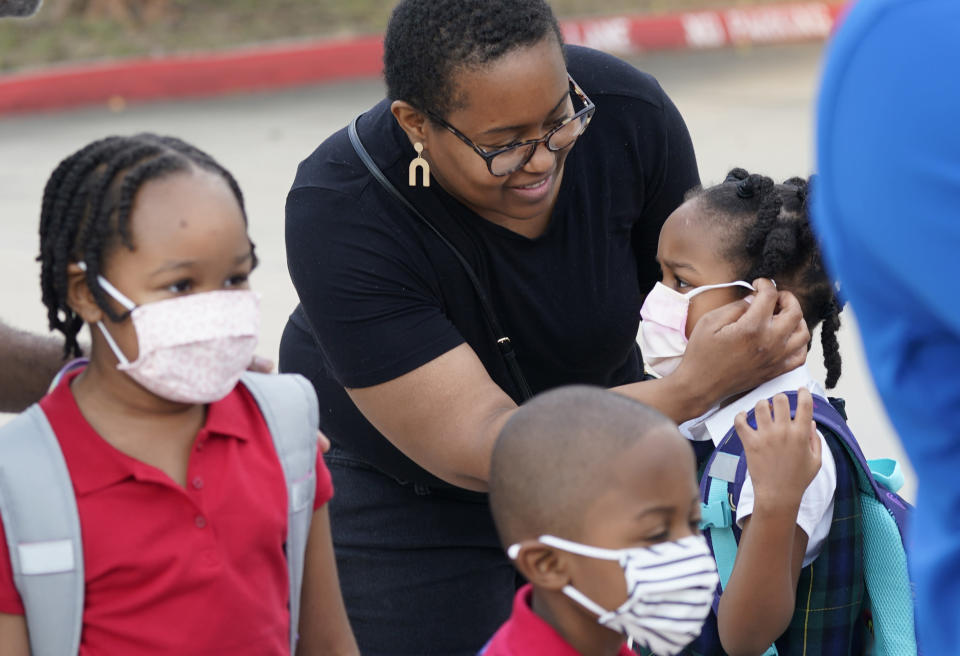 Leandra Walker, center, helps her daughter Mila Walker, 5, with her mask before she enters school with her siblings Olivia, 7, left, and her twin Max for the first day of classes in Richardson, Texas, Tuesday, Aug. 17, 2021. Despite Texas Gov Greg Abbott's executive order banning mask mandates by local officials, the Richardson Independent School District and many others across the state are requiring masks for students. (AP Photo/LM Otero)
