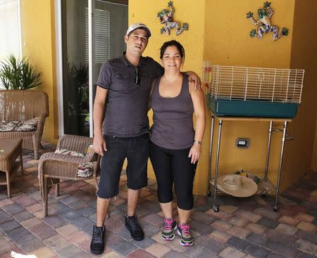 Alain Izquierdo (L), a Havana butcher and one of 15 survivors of the 32 Cuban migrants who were left adrift in Caribbean waters during their voyage, poses with his aunt Amarilis Barrios after speaking with Reuters at his uncle's home in Port St. Lucie, Florida, October 3, 2014. REUTERS/Rickey Rogers
