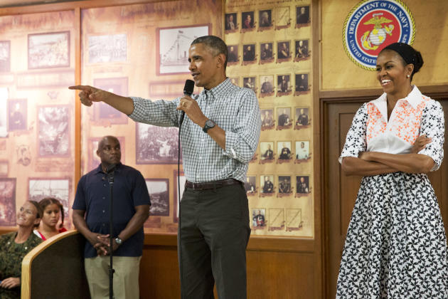 President Obama, with first lady Michelle Obama, points toward a child in the audience as he greets troops and their families on Christmas Day, Thursday, Dec. 25, 2014, at Marine Corps Base Hawaii in Kaneohe Bay, Hawaii.. (AP Photo/Jacquelyn Martin)