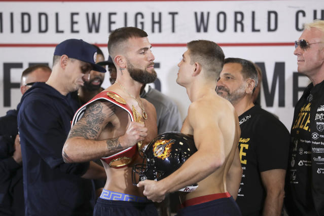 Caleb Plant, front left, and Vincent Feigenbutz , front right, face off Friday, Feb. 14, 2020, during the weigh-in for the IBF super middleweight title in Nashville, Tenn. The fight is scheduled for Saturday, Feb. 15. (AP Photo/Mark Humphrey)