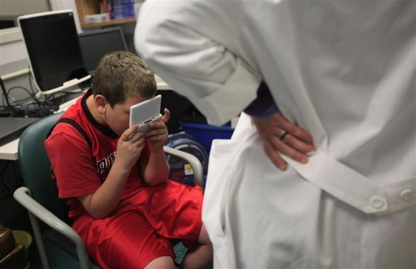 Parker Roos, who suffers from Fragile X, hides his face in his electronic game as he is asked questions by the doctor during a check up at the Fragile X Clinic and Research Program at Rush University Medical Center in Chicago, April 11, 2012.