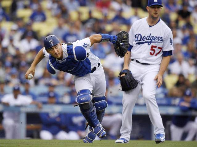 Los Angeles Dodgers catcher Austin Barnes, left, throws out San Francisco Giants' Alen Hanson at first as starting pitcher Alex Wood, right, watches during the third inning of a baseball game Saturday, June 16, 2018, in Los Angeles. (AP Photo/Mark J. Terrill)