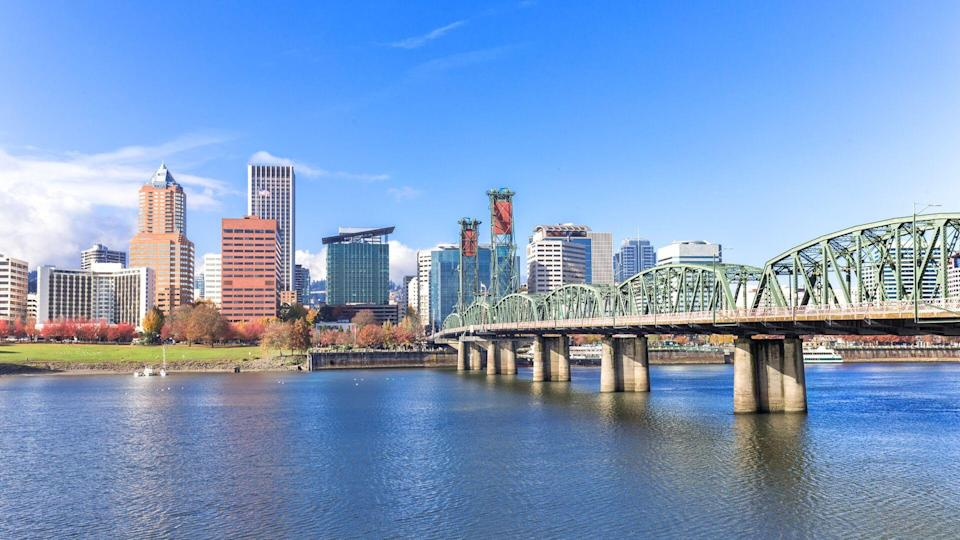 steel bridge over water with cityscape and skyline in portland.