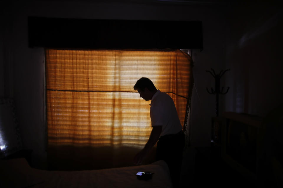 """Claudio Rojas, who was deported from the U.S. in 2019, is silhouetted against a curtained window of his home in Moreno, Argentina, Saturday, May 8, 2021. Rojas says he feels better since Trump left office, but he still lives with anxiety and can't sleep some nights. """"I am not in a detention center, but I feel like I am in jail in my own apartment. I am in Argentina, but I feel I am a foreigner. I can't adapt,"""" said Rojas. (AP Photo/Natacha Pisarenko)"""