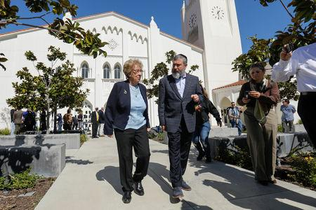 Auschwitz survivor Eva Schloss, stepsister of Holocaust diarist Anne Frank, walks with Chabad Rabbi Reuven Mintz at Newport Harbor High School after speaking with a group of students seen in viral online photos giving Nazi salutes over a swastika made of red cups that sparked outrage in Newport Beach, California, U.S., March 7, 2019. REUTERS/Mike Blake