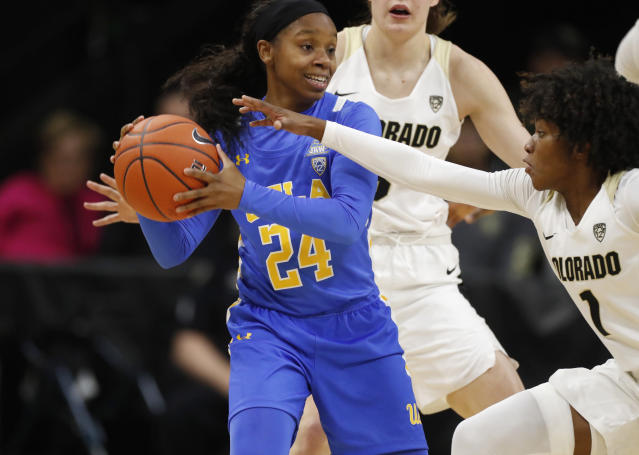 UCLA guard Japreece Dean, front left, looks to pass the ball as Colorado guards Jaylyn Sherrod, front right, and Emma Clarke defend in the first half of an NCAA college basketball game Sunday, Jan. 12, 2020, in Boulder, Colo. (AP Photo/David Zalubowski)