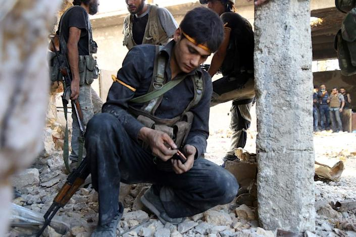 A rebel fighter reloads his weapon during clasahes with regime forces in Ramussa on the southwestern edges of Aleppo on August 6, 2016 (AFP Photo/Fadi A-Halabi)