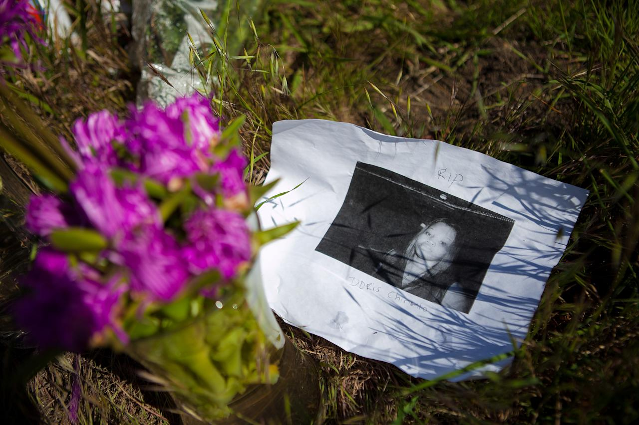 A photo of victim Doris Chibuko rests next to flowers at a memorial in front Oikos University where a gunman had gone on a shooting rampage, April 4, 2012 in Oakland, California. Six students and one employee were killed on Monday when a gunman opened fire at Christian-based Oikos University. The suspect One Goh, a former nursing student at the school, was arrested shortly after the shooting and is expected to make his first court appearance.  (Photo by Jonathan Gibby/Getty Images)