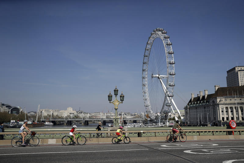 """A family space themselves apart as they cycle over Westminster Bridge past the London Eye ferris wheel in London, Friday, April 10, 2020. In a statement Thursday, a spokesman at 10 Downing Street said British Prime Minister Johnson """"has been moved this evening from intensive care back to the ward, where he will receive close monitoring during the early phase of his recovery."""" The new coronavirus causes mild or moderate symptoms for most people, but for some, especially older adults and people with existing health problems, it can cause more severe illness or death. (AP Photo/Matt Dunham)"""