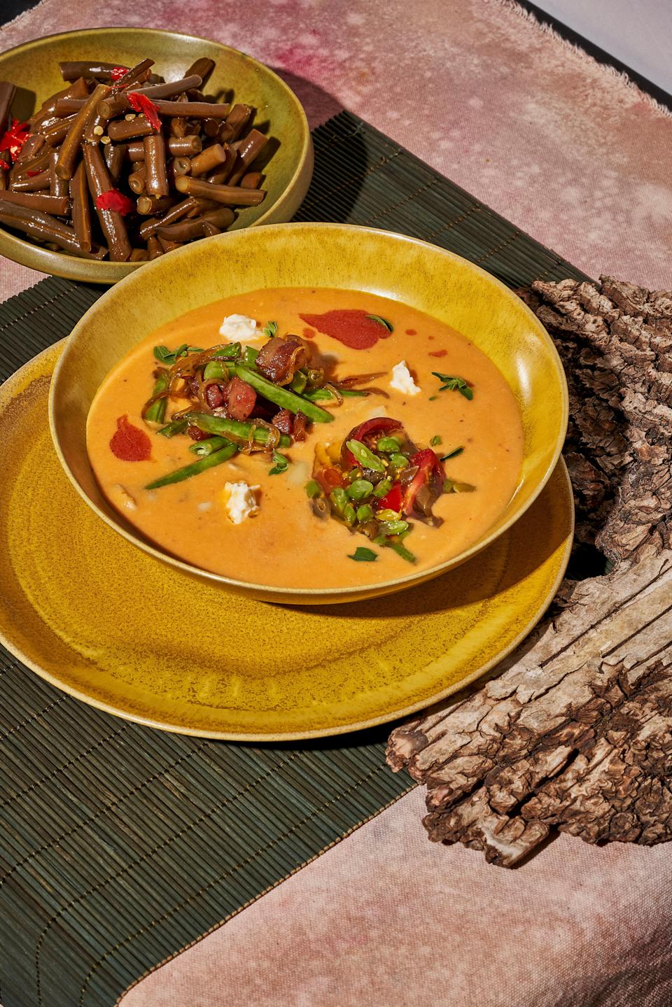 """A tangle of baked Romano beans and bacon (plus feta and a crisp pickled green bean salad) add a textural flourish to this warming puréed white bean and tomato soup. One recommendation: don't even think about skipping the <a href=""""https://www.epicurious.com/ingredients/tomato-brown-butter-peak-tomatoes-year-round-article?mbid=synd_yahoo_rss"""" rel=""""nofollow noopener"""" target=""""_blank"""" data-ylk=""""slk:tomato brown butter"""" class=""""link rapid-noclick-resp"""">tomato brown butter</a>. <a href=""""https://www.epicurious.com/recipes/food/views/summer-bean-soup-with-tomato-brown-butter-cortney-burns?mbid=synd_yahoo_rss"""" rel=""""nofollow noopener"""" target=""""_blank"""" data-ylk=""""slk:See recipe."""" class=""""link rapid-noclick-resp"""">See recipe.</a>"""