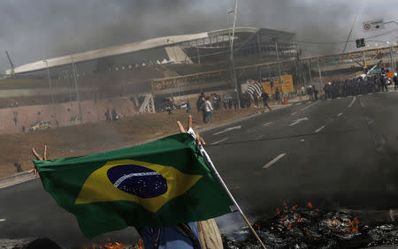 A member of Brazil's Homeless Workers' Movement blocks a road during a protest in front of Sao Paulo's World Cup stadium in this May 15, 2014 file photo. REUTERS/Nacho Doce/Files