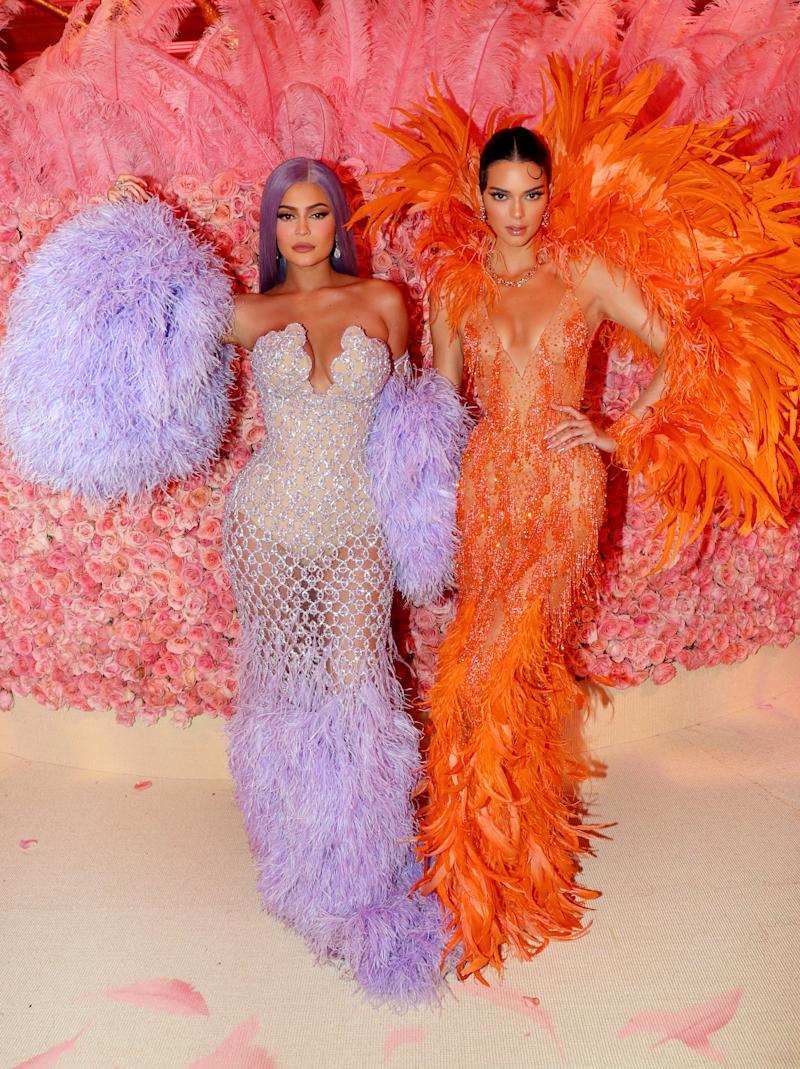 A photo of Kylie Jenner wearing a purple dress and Kendall Jenner wearing an orange dress at the 2019 Met Gala Celebrating Camp: Notes on Fashion at Metropolitan Museum of Art on May 06, 2019 in New York City.