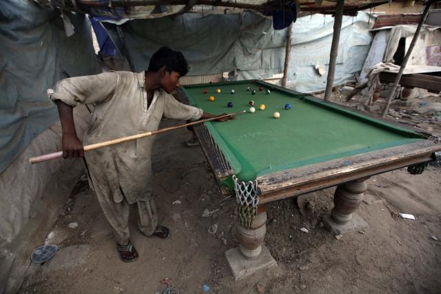A boy plays snooker at a slum on the outskirts of Karachi February 27, 2015. REUTERS/Athar Hussain (PAKISTAN - Tags: SOCIETY)