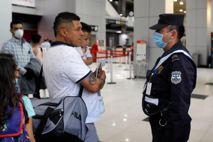 A passenger asks for information from a police officer after El Salvador's President Bukele ordered the closing of the airport in San Luis Talpa