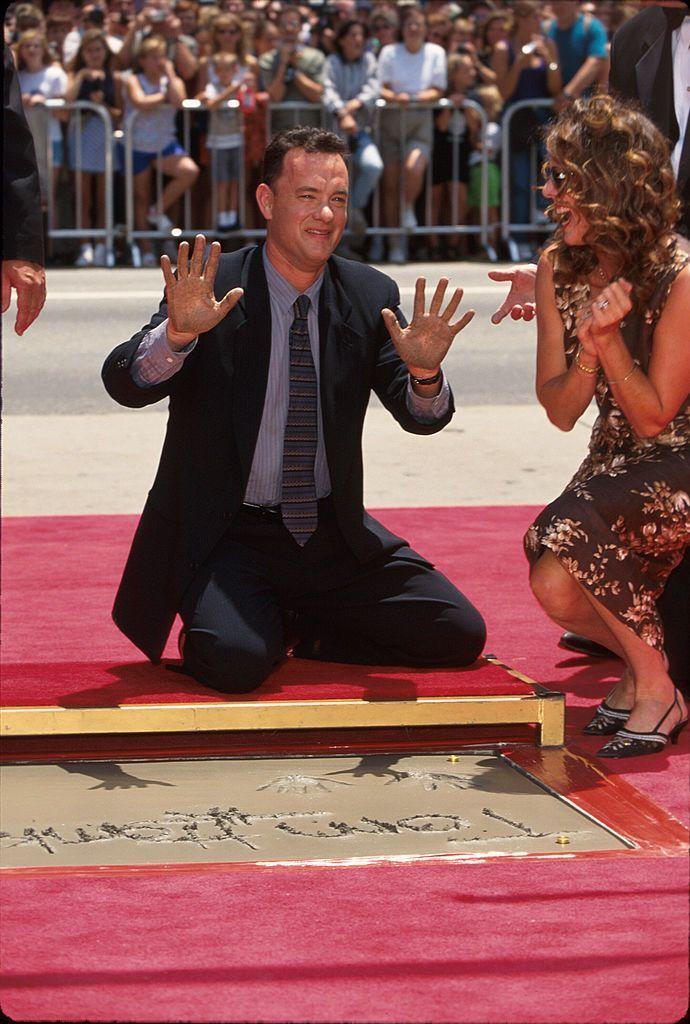 """<p>While Tom got his hands dirty for his hand and footprints ceremony at Mann's Chinese Theatre on July 23, he threatened to wipe them on a laughing Rita. She's his """"best friend,"""" Tom <a href=""""http://www.oprah.com/omagazine/Oprah-Interviews-Tom-Hanks"""" rel=""""nofollow noopener"""" target=""""_blank"""" data-ylk=""""slk:told Oprah"""" class=""""link rapid-noclick-resp"""">told Oprah</a>. """"In addition to being my lover. And it has been that way from the very beginning. We laugh just as much now at two in the morning as we always have. And we fight less and less.""""</p>"""