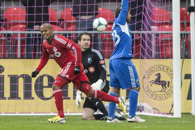 Toronto FC 's Robert Earnshaw, left, turns to celebrate after scoring the game's opening goal as Montreal Impact goalkeeper Troy Perkins, center, and Herman Bernadello look on during the first half of an MLS soccer game in Toronto on Saturday, Oct. 26, 2013. (AP Photo/The Canadian Press, Chris Young)