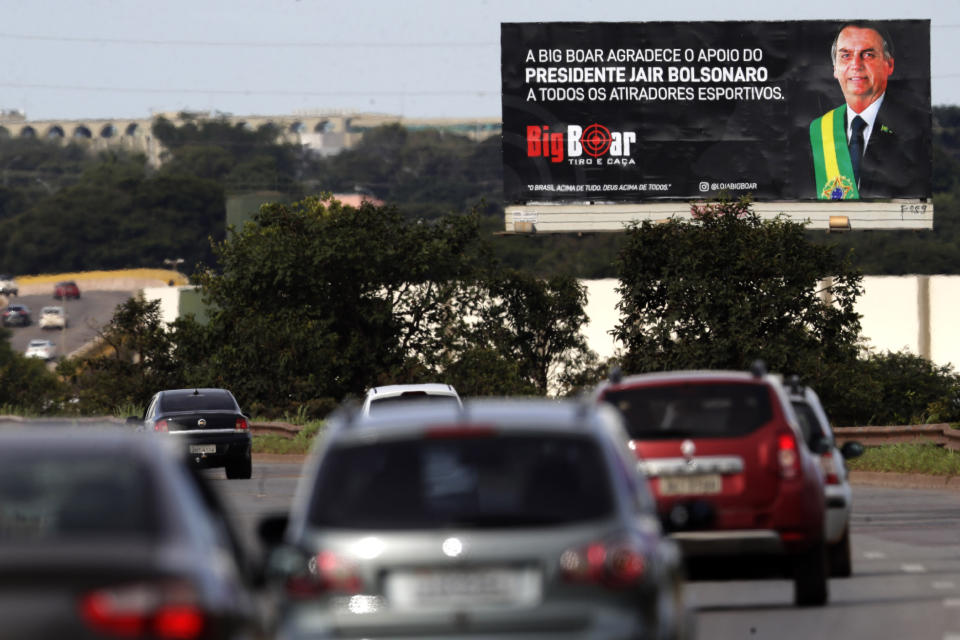 """A billboard towering over traffic on an access road promotes the Big Boar gun shop plastered with an image of Brazil's President Jair Bolsonaro and a message that reads in Portuguese: """"Big Boar thanks President Jair Bolsonaro for his support of all shooters,"""" in Brasilia, Brazil, Friday, March 5, 2021. Bolsonaro is pushing to deliver on his promise to arm every person that wants it. (AP Photo/Eraldo Peres)"""