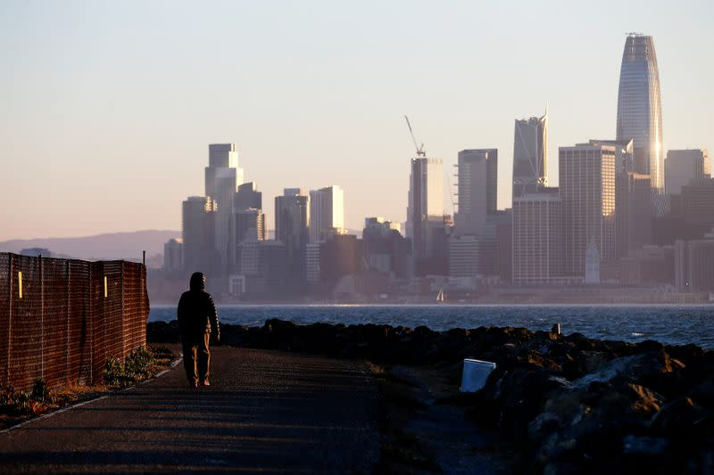 FILE PHOTO: The San Francisco skyline is seen behind a woman as she walks past a condemned area on Treasure Island, near San Francisco
