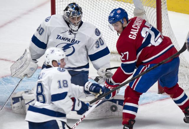 Montreal Canadiens' Alex Galchenyuk looks for the rebound on a save by Tampa Bay Lightning goalie Ben Bishop as Lightning's Ondrej Palat watches during the second period of an NHL hockey game Tuesday, Nov. 12, 2013, in Montreal. (AP Photo/The Canadian Press, Paul Chiasson)
