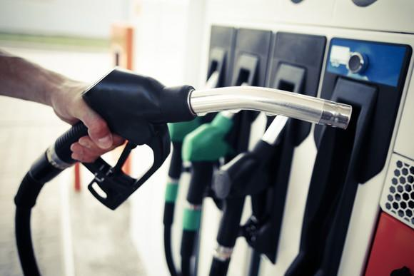 A man's hand holds a gas nozzle in front of a gas pump