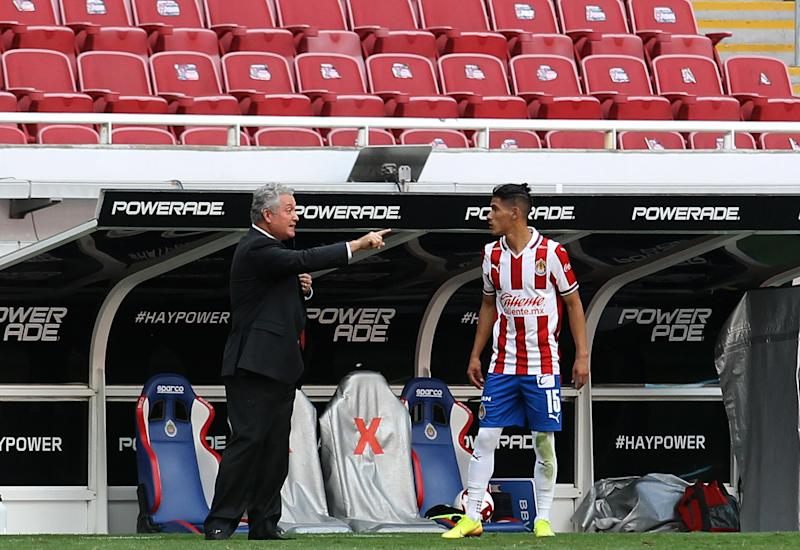 Guadalajara's coach Victor Vucetich (L) gives instructions to his player Uriel Antuna during their Mexican Apertura tournament football match against Atletico San Luis, at the Akron stadium, in Guadalajara, Jalisco State, Mexico, on August 15, 2020, during the COVID-19 coronavirus pandemic. (Photo by Ulises Ruiz / AFP) (Photo by ULISES RUIZ/AFP via Getty Images)