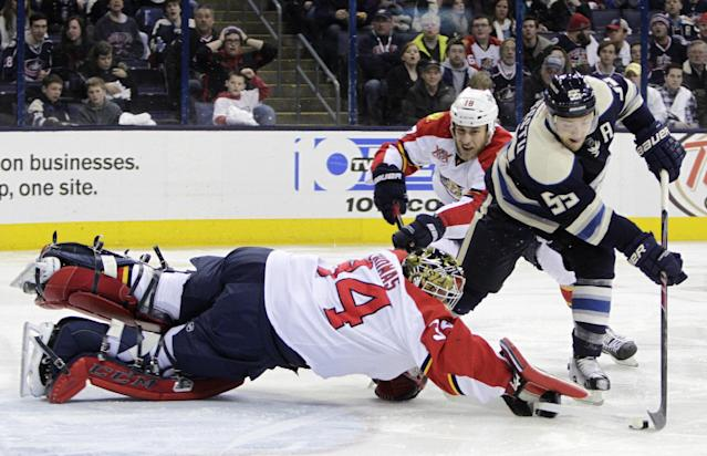 Florida Panthers' Tim Thomas, left, makes a save as teammate Shawn Matthias, center, and Columbus Blue Jackets' Mark Letestu try to control the puck during the second period of an NHL hockey game on Saturday, Feb. 1, 2014, in Columbus, Ohio. (AP Photo/Jay LaPrete)