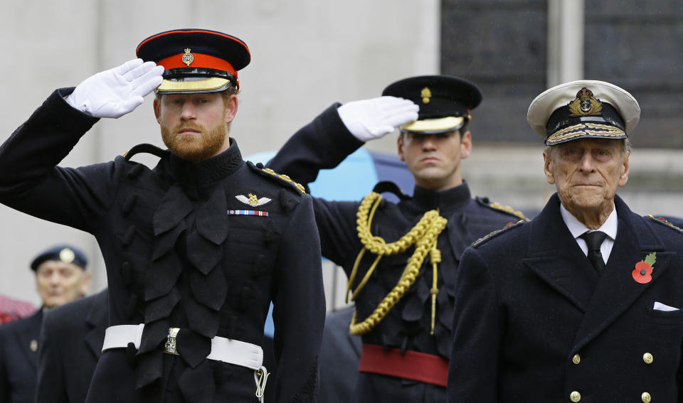 Britain's Prince Harry (L) salutes next to his grandfather Prince Philip, Duke of Edinburgh, during a visit to the Field of Remembrance at Westminster Abbey in central London on November 5, 2015. The Duke of Edinburgh and Prince Harry each placed a Cross of Remembrance for Unknown British Soldiers from the First and Second World Wars. AFP Photo/Kirsty Wigglesworth/POOL (Photo by KIRSTY WIGGLESWORTH / POOL / AFP) (Photo by KIRSTY WIGGLESWORTH/POOL/AFP via Getty Images)