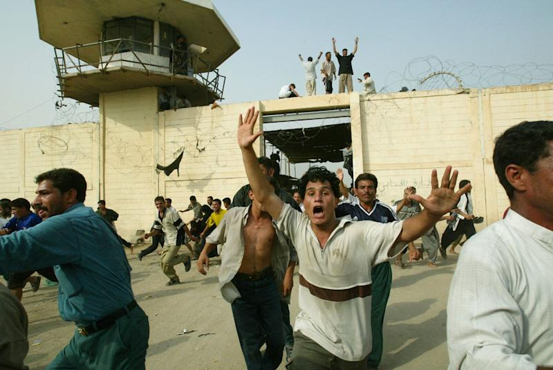 FILE - In this Sunday, Oct. 20, 2002 file photo, hundreds of Iraqis storm the Abu Ghraib jail 35 kilometers (21 miles) northwest of Baghdad, following the announcement by President Saddam Hussein that most prisoners were going to be freed. An Iraqi Justice Ministry official said Wednesday, April 16, 2014 that this week's closure of the infamous Abu Ghraib prison west of Baghdad is temporary and that it will be reopened once the security situation in the surrounding area is stable. The closure is the latest chapter in the history of the prison, which during Saddam Hussein's rule was one of the main facilities for jailing and executing his opponents. After the U.S.-led invasion that toppled Saddam, Abu Ghraib became notorious once again, for a 2004 scandal over abuses of detainees by American guards. (AP Photo/Jerome Delay, File)