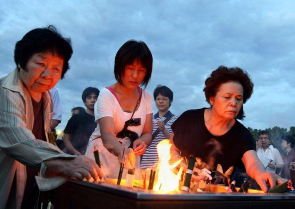 Japanese people burn incenses and pray in front of a monument for atomic bomb vicitims at the Hiroshima Peace Memorial Parkon August 6, 2012 in Hiroshima. Japan. Japan marks the 67th anniversary of the first atomic bomb that was dropped on Hiroshima by the United States on August 6, 1945, killing an estimated 70,000 people instantly with many thousands more dying over the following years from the effects of radiation. Three days later another atomic bomb was dropped on Nagasaki, ending World War II. (Photo by Buddhika Weerasinghe/Getty Images)