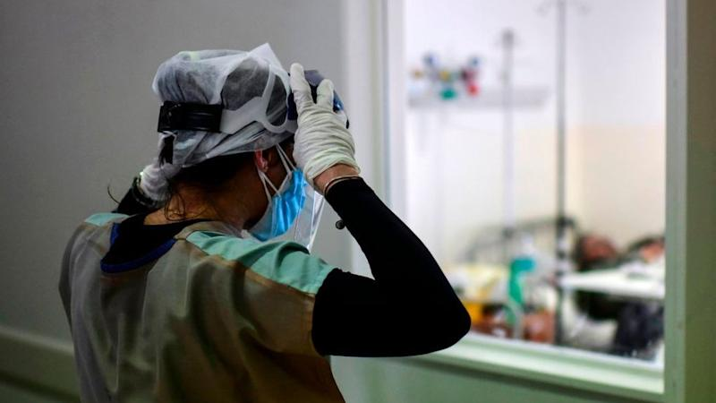 Doctor Analia Mondo looks at a patient infected with the new coronavirus at the Doctor Alberto Antranik Eurnekian Public Hospital in Ezeiza, in the outskirts of Buenos Aires